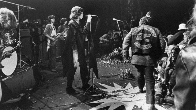 Mick Jagger sings at the Altamont Rock Festival at Livermore, Calif. on Saturday, December 6, 1969 while Hells Angels cross stage during melee to help fellow motorcyclists. The Rolling Stone hired the Hells Angels to police the concert for $500 worth of beer. (AP Photo)